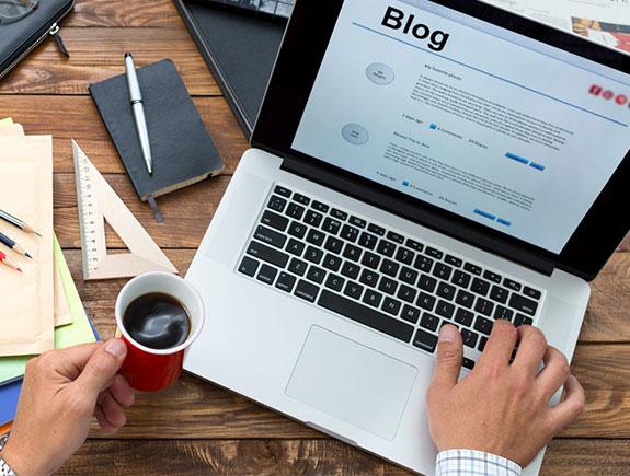 Ruka na tastaturi laptopa i kafa u crvenoj šoljici
