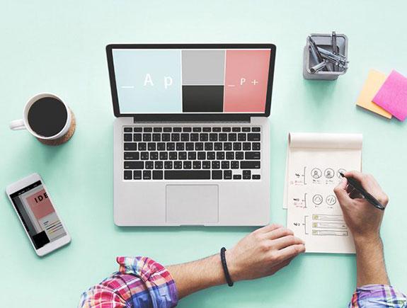 Laptop, mobilni telefon, kafa i ruke koje pišu
